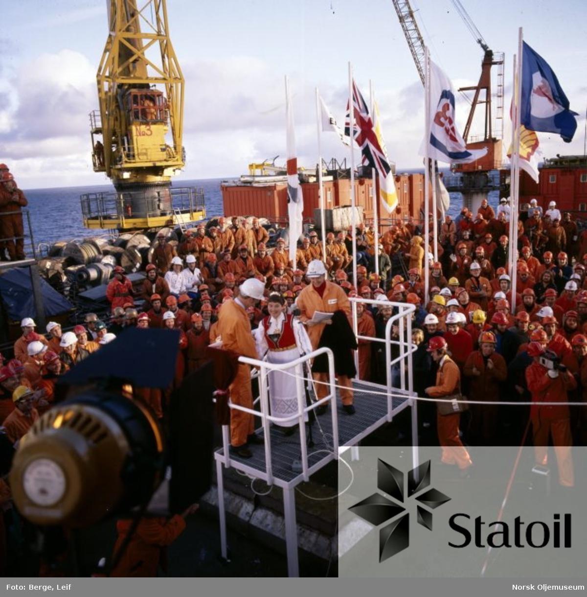 Statfjord A er nettopp døpt av Oddbjørg Kloster, og gratuleres her av statsminister Odvar Nordli.  Statoildirektør Arve Johnsen står t.h. mens en rekke ansatte og andre innbudte gjester fyller dekket.