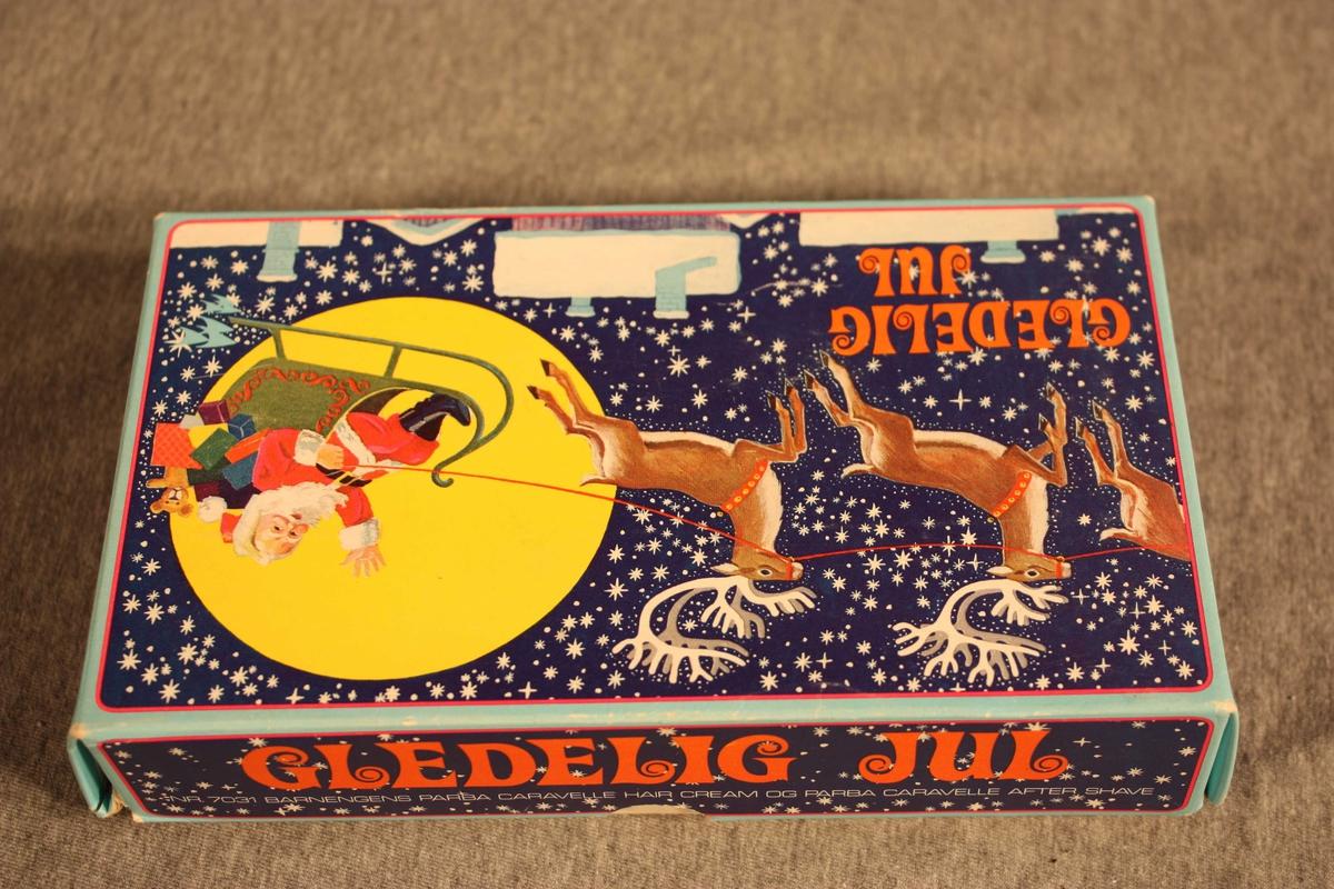 Julemotiv på loket av øskja; stjernehimmel, snødekte hus, reinsdyr, nisse i slede. Gledeleg jul i raudt på oversida og alle fire kantane av loket.