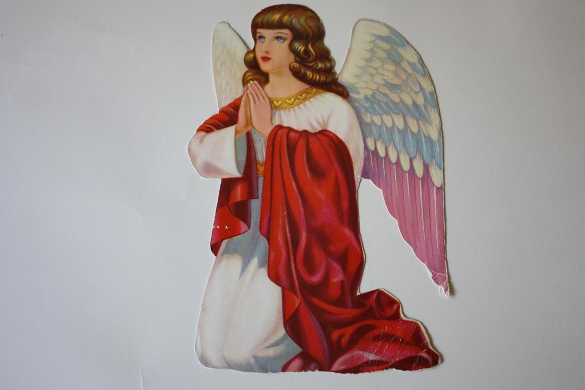 Knelande engel. Brunt halvlangt hår. Kvit kjole med gulldekor, raudt klede