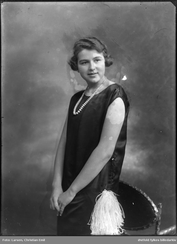 Portrett av ukjent ung kvinne med bobfrisyre, Charleston-kjole med fjærpynt og perlekjede, fotoatelier, 1926.