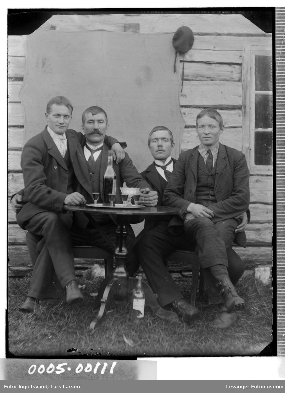 Gruppebilde av fire menn i festlig lag ved et bord med flasker og glass.