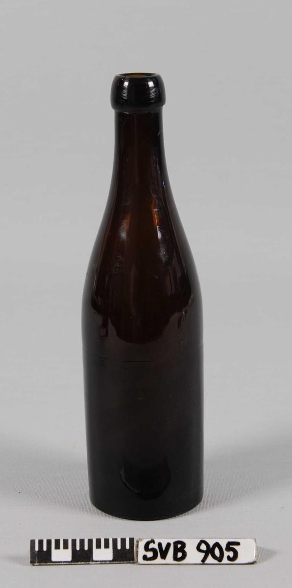 Drikkeflaske i brunt, klart glass. Slank kropp og lang hals med flat bunn. Klart avgrenset flasketut for propp av kork.