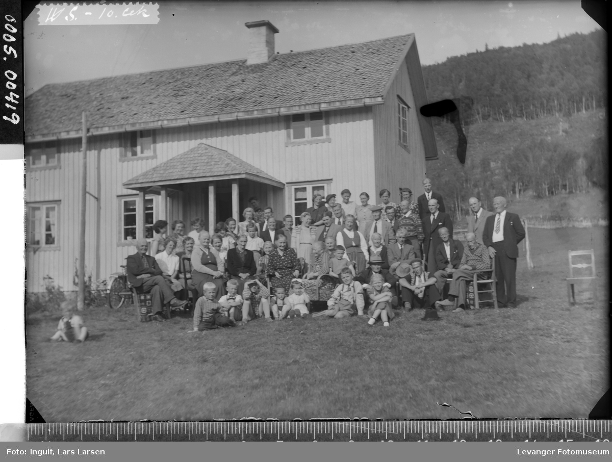 Gruppebilde av en stor gruppe mennesker, foran et våningshus som har deltatt på gudstjeneste.