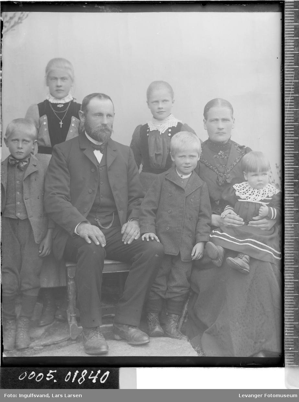 Gruppebilde av en mann, en kvinne, en ungdom og tre barn.