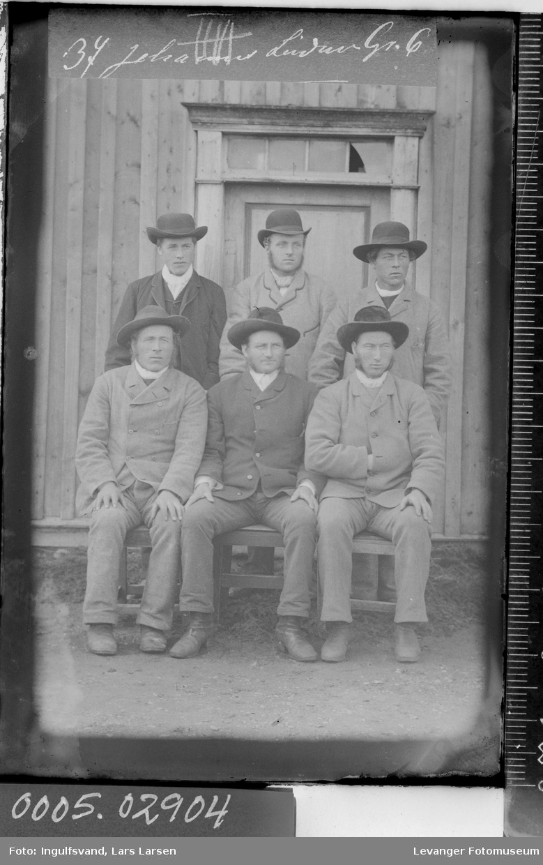 Gruppebilde av seks menn foran et inngangsparti.