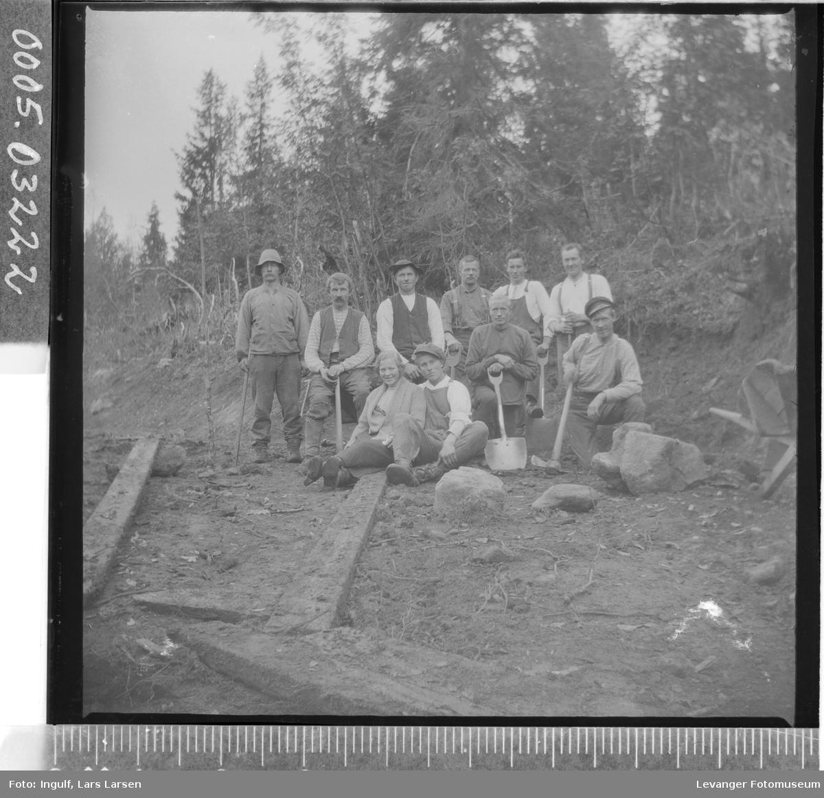 Gruppebilde av ni vegarbeidere og en kvinne.