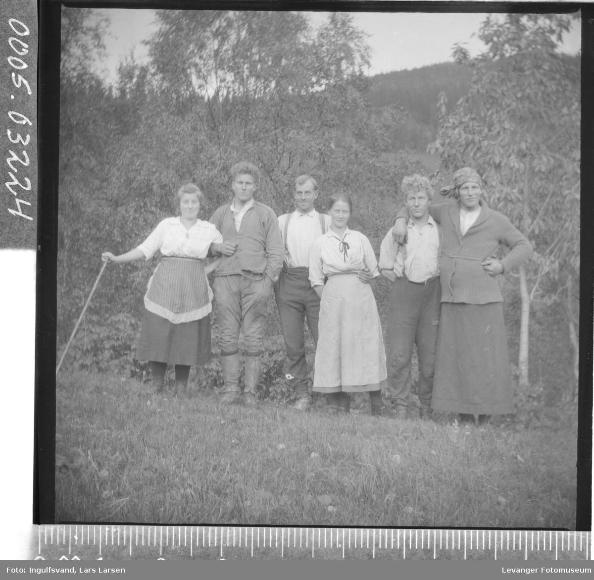 Gruppebilde av fire menn og to kvinner, hvorav en mann er utkledd som kvinne.