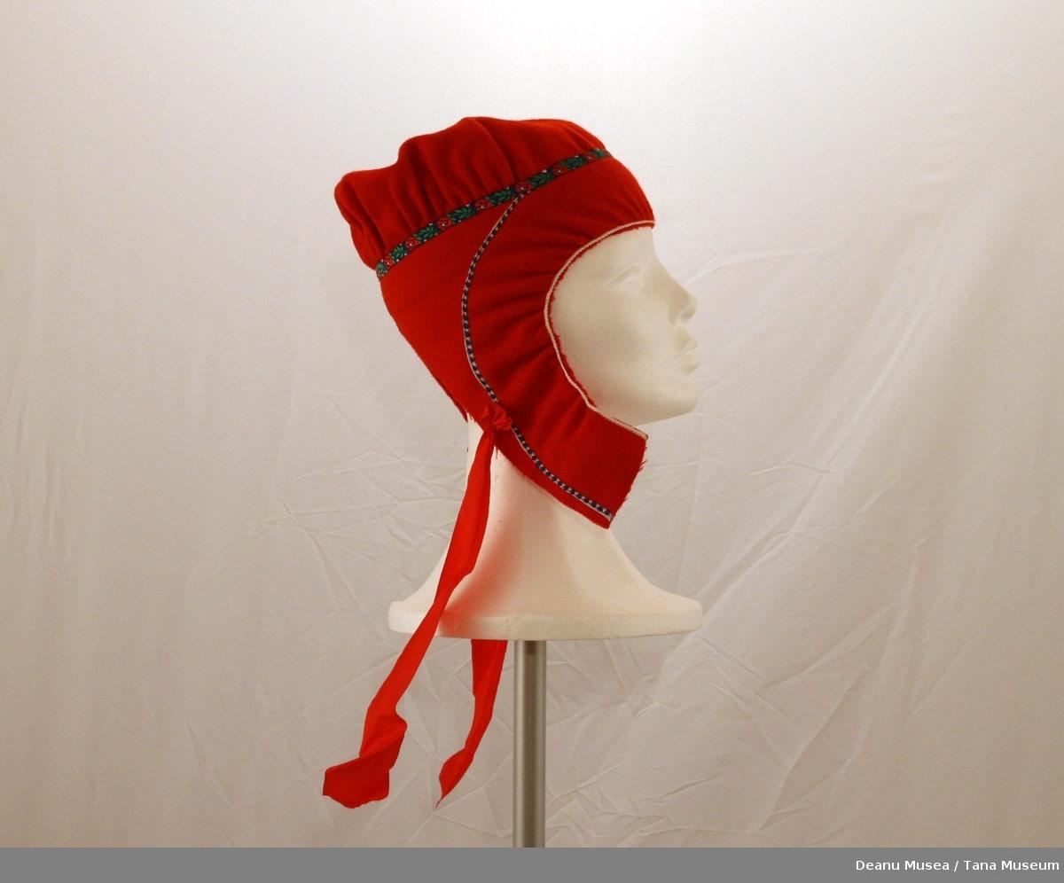 Rød samisk jentelue. Blå pyntebånd med roser på. Knytebånd av rød silke.