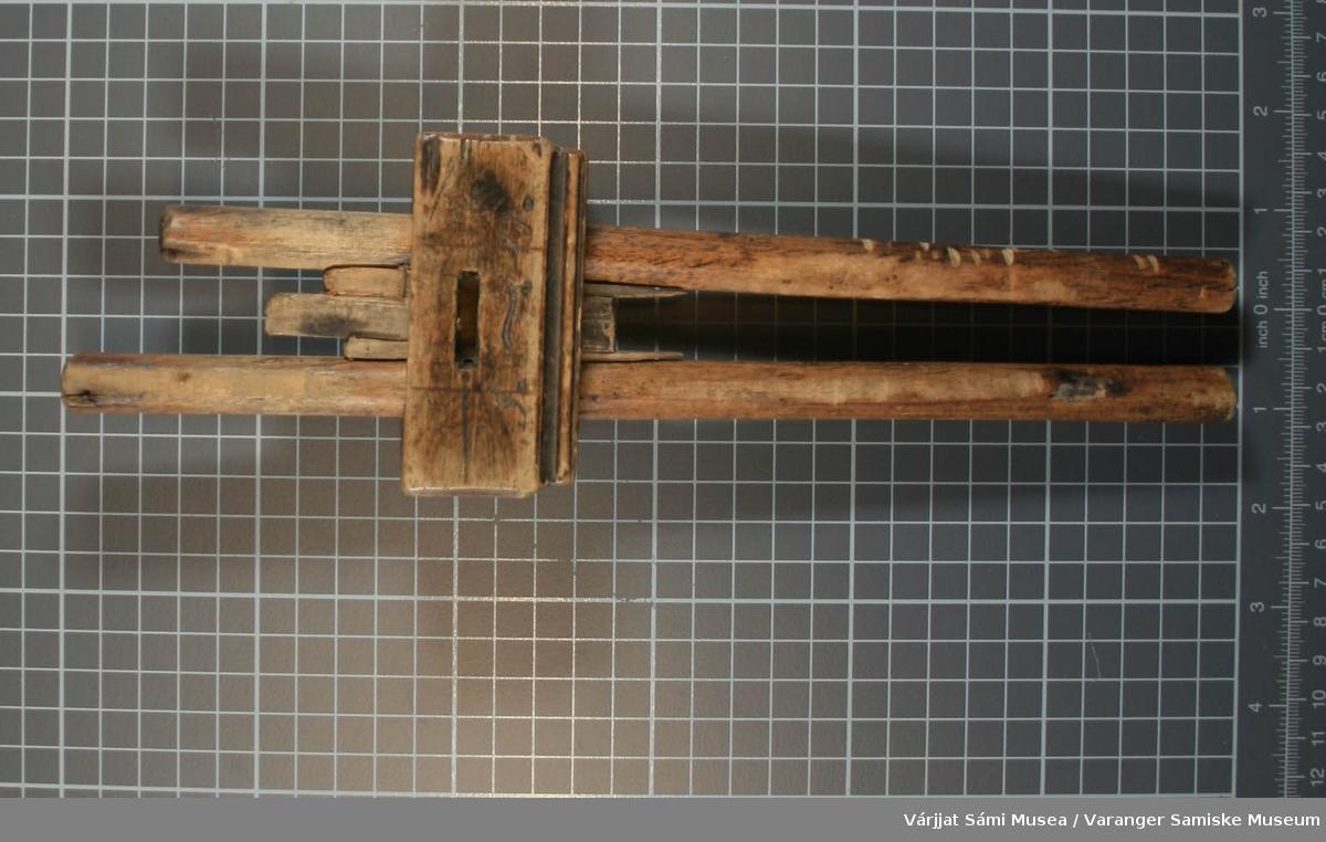 """Innretningen er et måleinstrument for trevirke. Ytterst på de to lengste pinnene var en spiker festet og skulle markere målet ved å """"rispe"""" spor i materialet. Selve """"klossen"""" har en inskripsjon på to av langsidene: """"1872"""" og """"A-O""""."""
