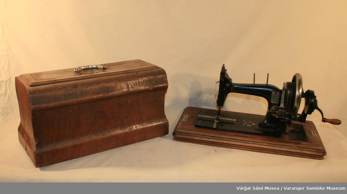 Symaskin med kasse. Nr. 777032. Symaskinen fungerer. Sokkelen av tre, resten av svart jern. Kassen har et blankt håndtak og dekor på toppen.