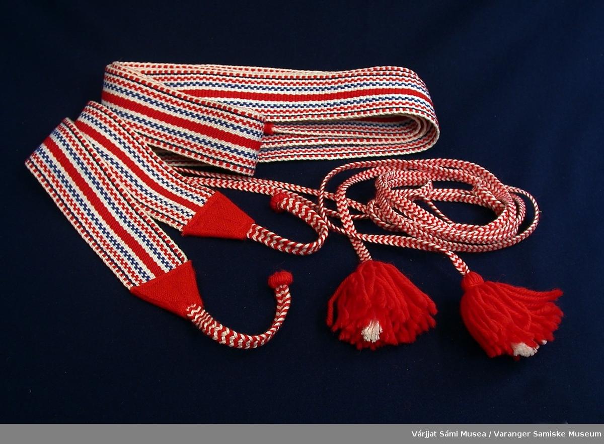 Et par vevde skallebånd med langsgående striper i rødt, hvitt og blått. I den ene enden av båndene er det korte, flettede snorer i rødt og hvitt. I den andre enden er det lange smale flettede snorer i rødt og hvitt med en dusk i enden.