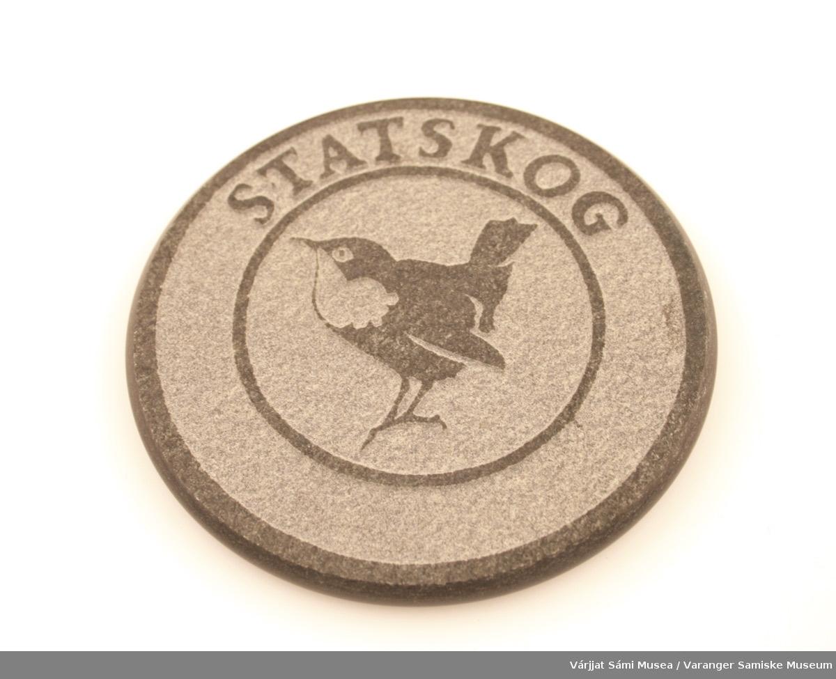 """Et rundt skilt av grå polert skifer med Fossekall motiv i midten rammet inn av to sirkler og tekst : """"Statskog"""". Pålimt oppheng på baksiden."""
