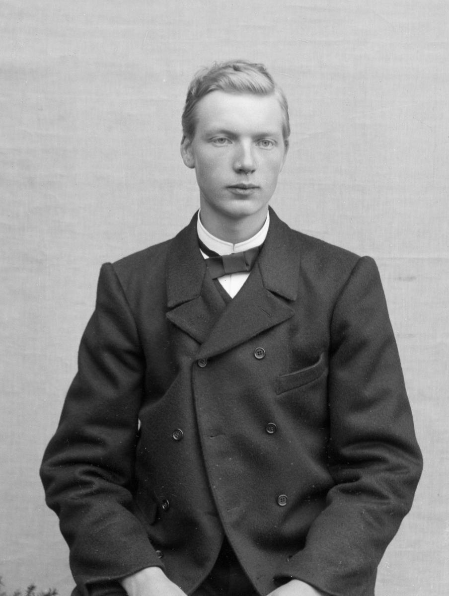 Dresskledd mann foran hvitt lerret
