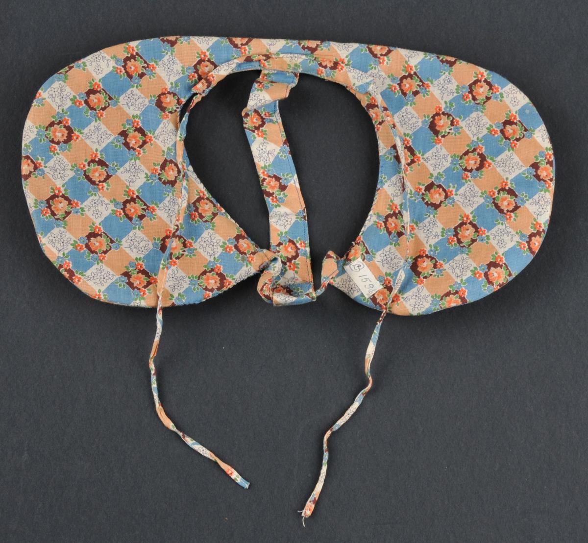 Rudd med innlegg (som truleg er av hattefilt eller papp). Form som eit brudelad, trekt med mønstra bomullstøy. Stiva opp med ståltråd rundt kantane. Påsett eit band for støtte oppå hovudet og eit band ved nakken. To smale band for binding i nakken. Bruka til å ha under skautet.