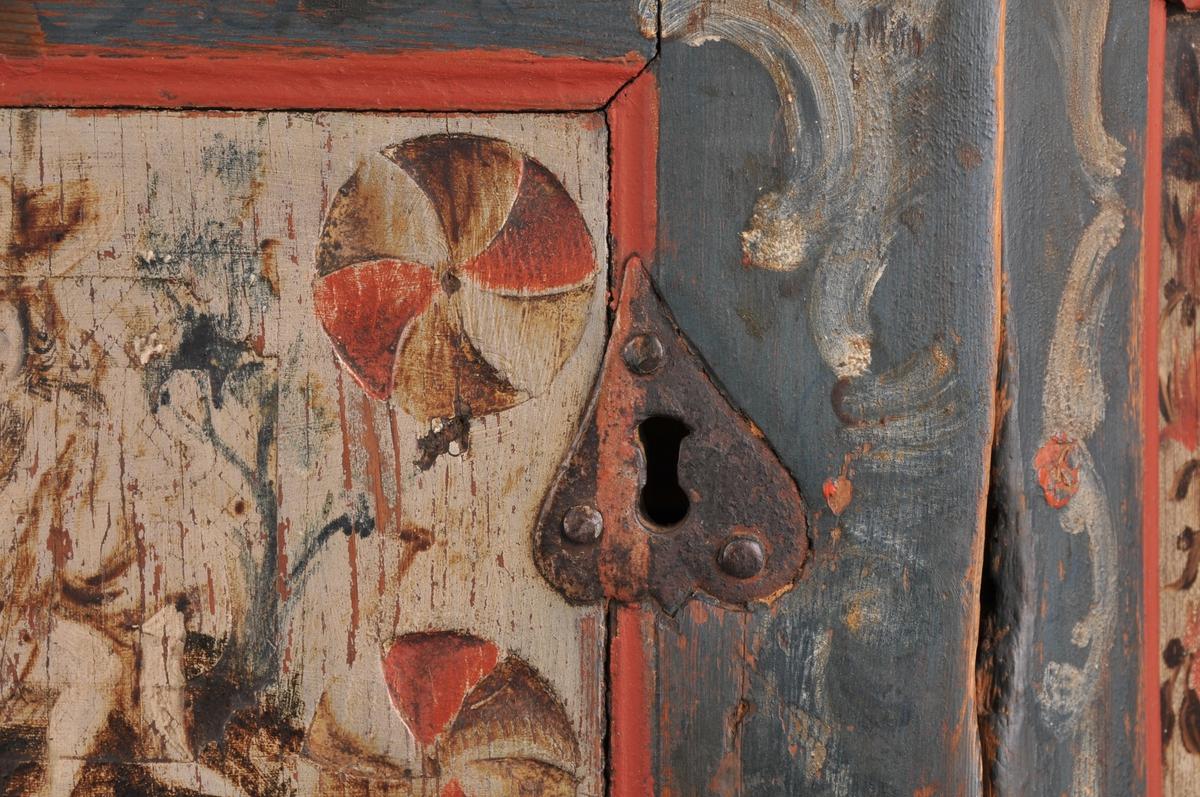 Hjørneskåp med to dører og opning i midten. Skåpet er blåmåla med raude kantar og rosemåling i kvitt, raudt og ulike blåtonar. På dei to øvste fyllingane på sidene er det måla blomsterurner. I midten ein person som sit.