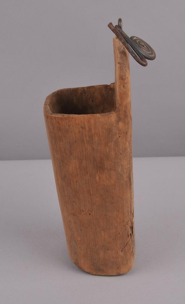 Skopp som er uthola av eit stykke tre, slitt, skada og reparert med trepluggar på to stader. Snodd ståltråd som er forma som ein krok, til oppheng.
