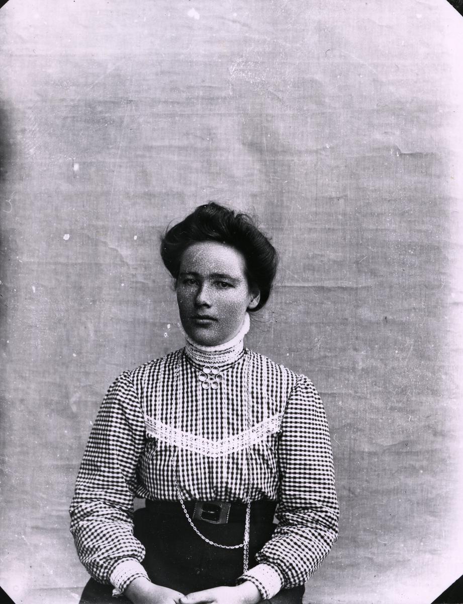 Kvinne kledd i rutete skjorte, lerretbakgrunn