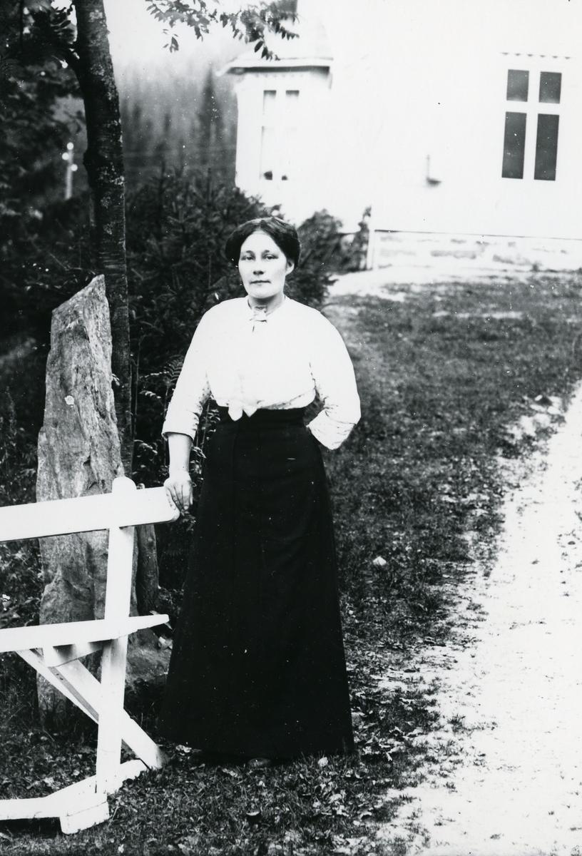 Kvinne avbildet ved benk, på vei, med hvit bygning i bakgrunnen