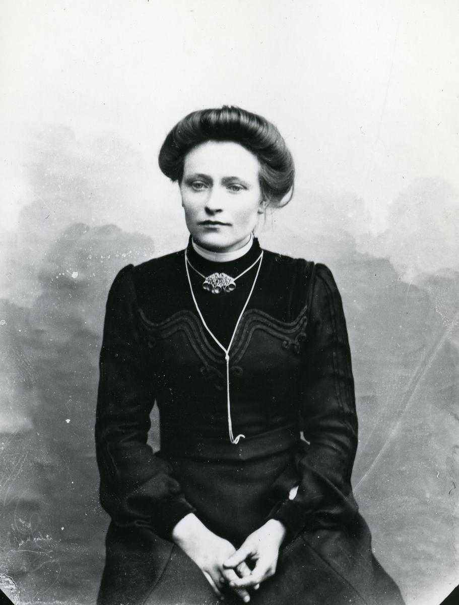 Kvinne kledd i mørk kjole med sølje, sittende foran lerret
