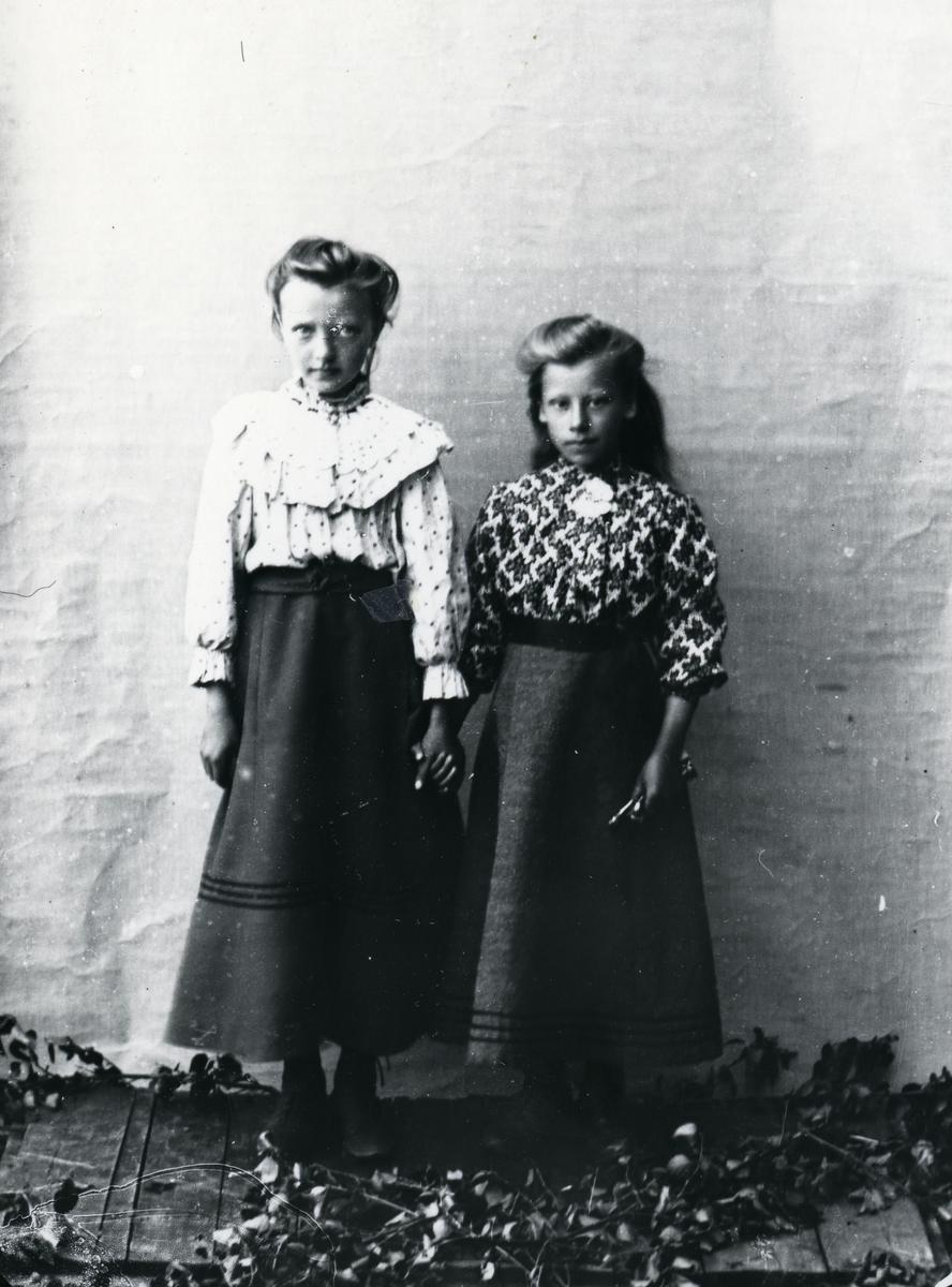 To jenter i mønstrete skjorter og mørke skjørt, stående foran lerret, holder hverandre i hendene