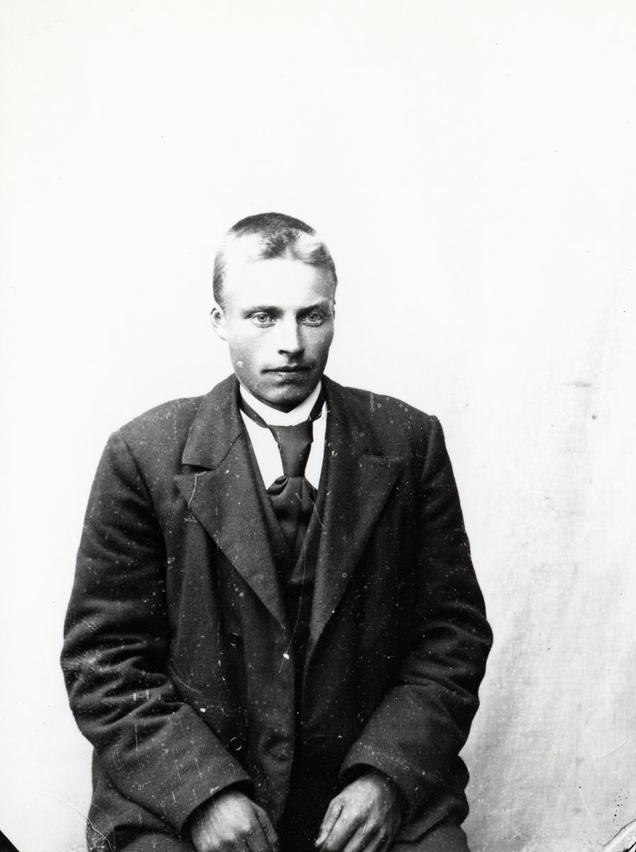Mann i halvfigur, sittende foran lerret
