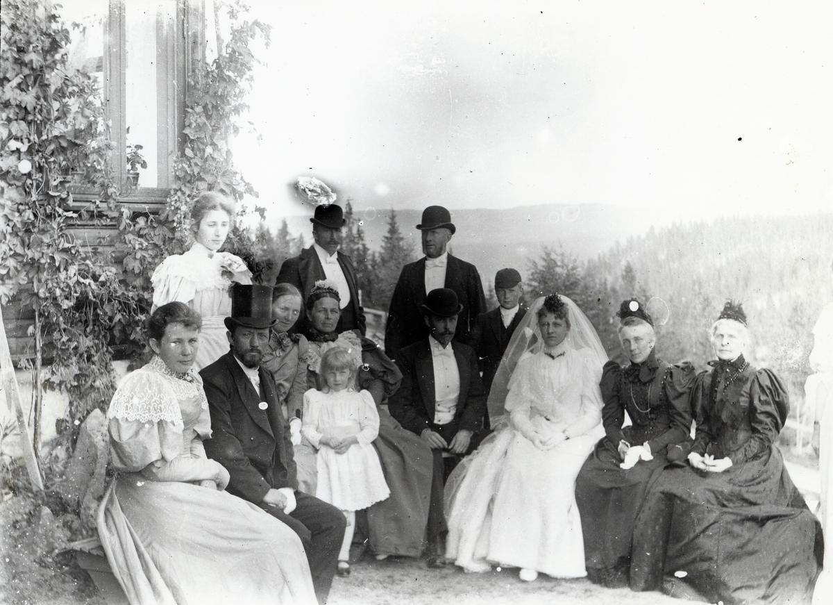 Gruppe mennesker oppstilt utenfor husvegg, brudepar i midten