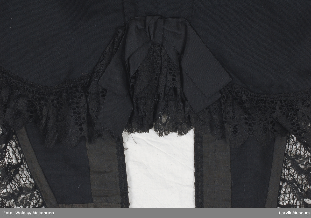 Form: hekter/hemper,form: rygg m midtsøm,innsvingete sidesømmer og tilbaketrukne skuldersømmer,ermeparti rynket til bolen,forstykkene ender i fliker,snørebånd på inn- siden av midjen,blondebesetning langs kantene,rysje av samme langs nedre kant,ripssløyfe midt bak nede vasket og glattet av AJ