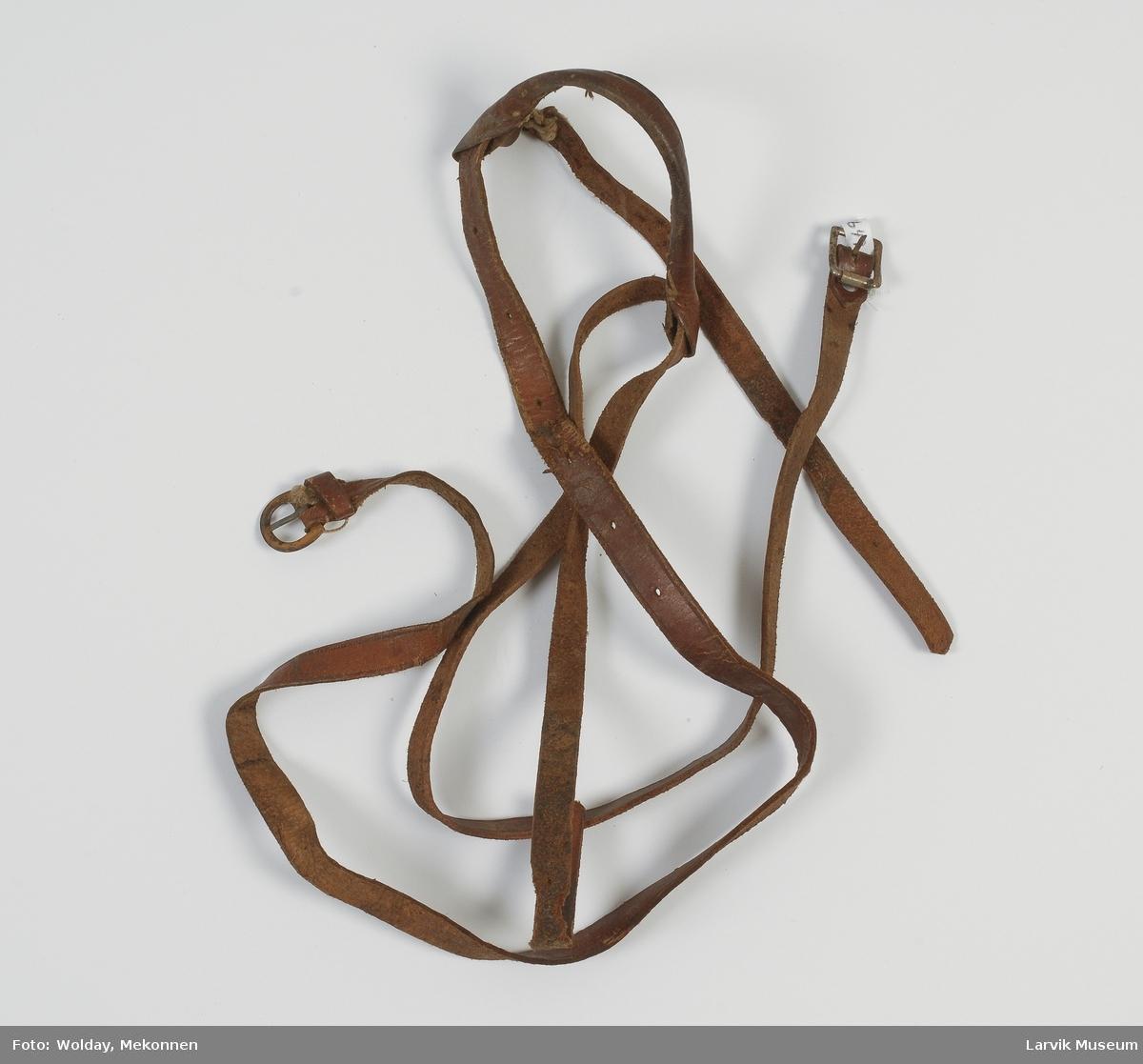 Form: To lange remmer med spenne i den ene enden, som holdes sammen av en rundsydd rem.