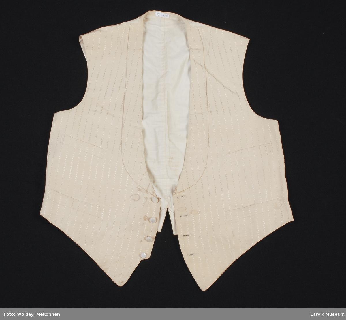 Form: Vest. 4 perlemorsknapper foran. 4 lommer. Mønstervevd stoff. Spenne bak for stramming.