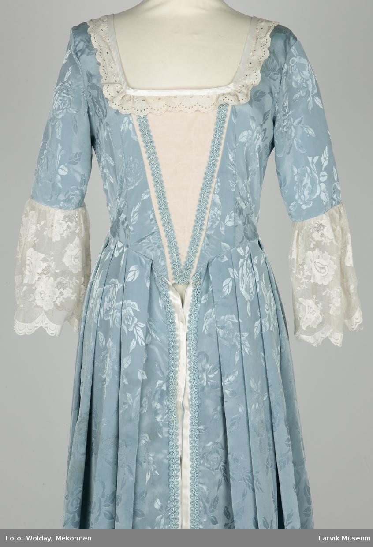 Lang kjole i lyseblå imitert silkeog blonder. Brukt som kjole/kappe under stivt underskjørt.