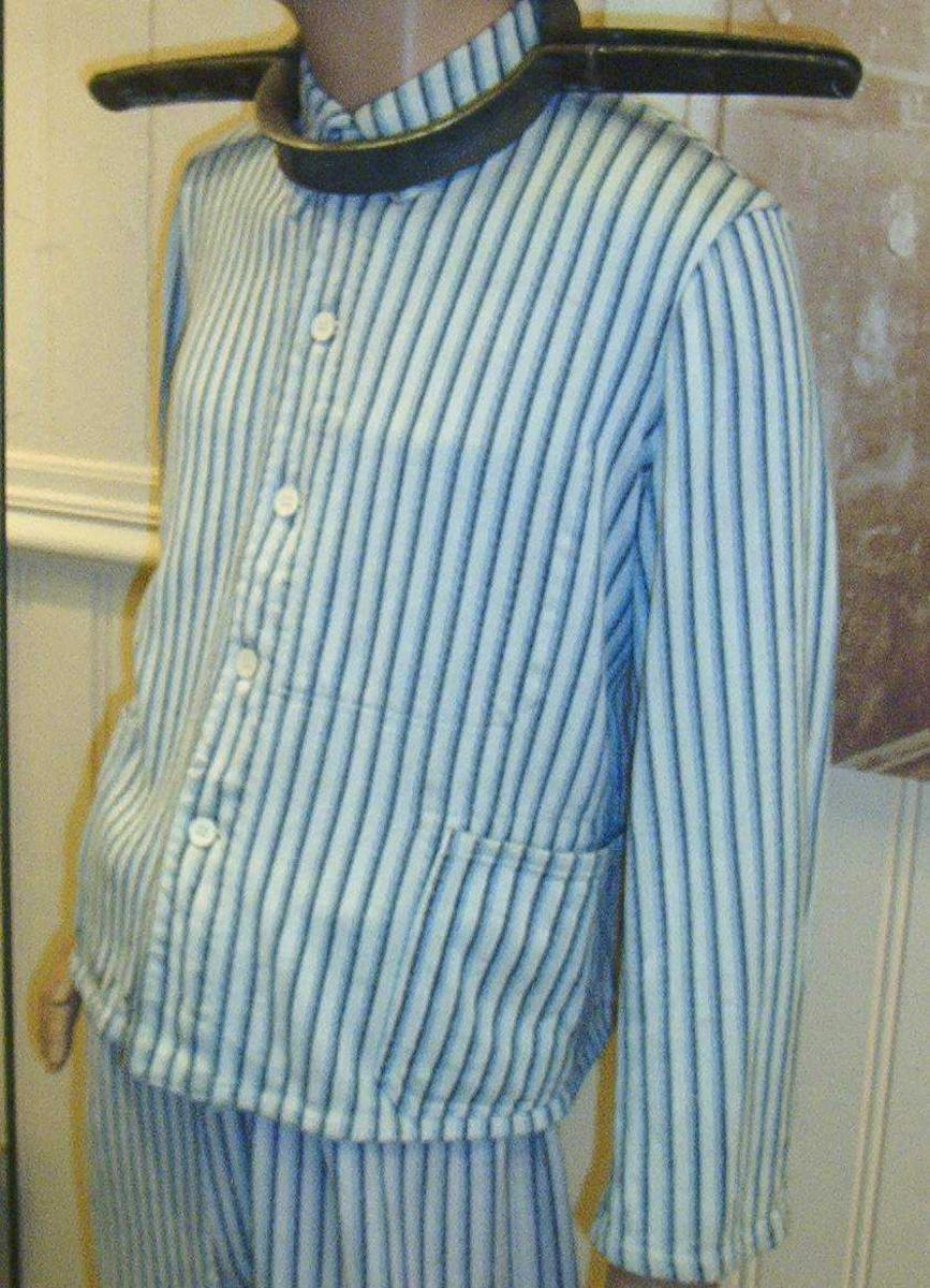 Enkel langermet bomullsskjorte med krave. Vertikalt stripemønster i blått og hvitt. To enkle lommer og fem knapper i front.