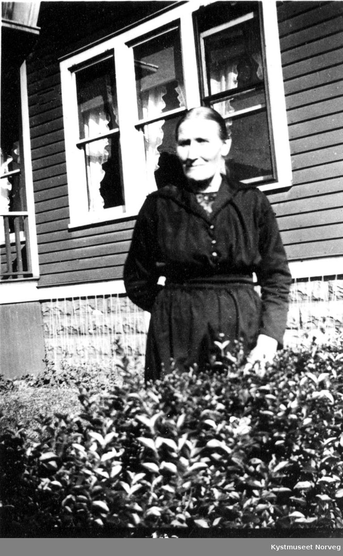 Gammel ukjent kvinne foran hus