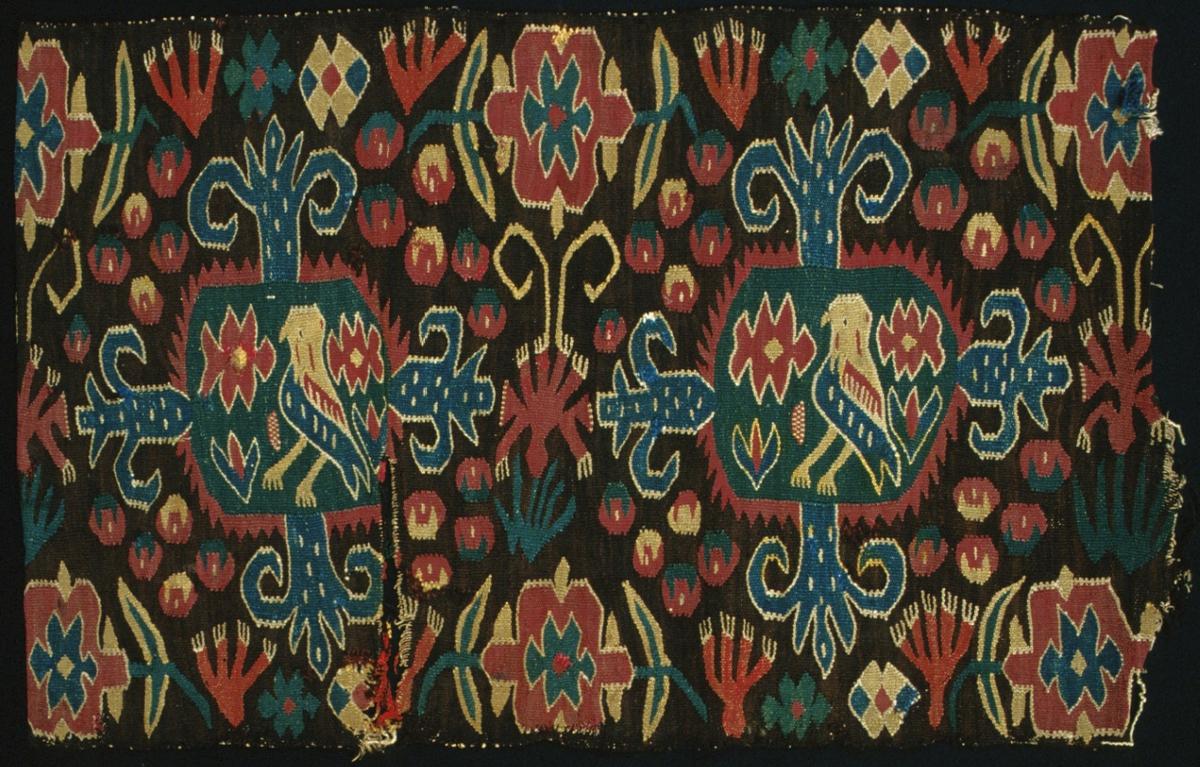 """Bänkdyna """"Den innelykta fågeln"""" vävd i flamsk. I mönstret framställs två sexkantiga figurer med taggig ytterkontur med en i mitten stående fågel och blommor. I övrigt är ytan mönstrad med stiliserade blommor och blad. Brun botten skiftande i två olika nyanser. Mönster i blårött, gulrött, blått, gult, grönt och naturvitt.  Varp i 2-trådigt s-tvinnat lingarn, 5 trådar/cm. Inslag i 2-trådigt ullgarn. Varptrådarna är av längs ett långt snitt från ytterkanten och 280 mm in på dynan. Baksida till dynan saknas. Märkt på avigsidan med påsydd lapp: """"Harjagers h.d No 248."""""""