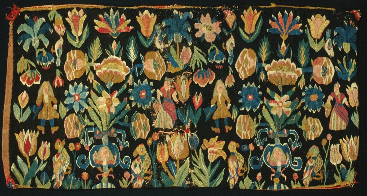 """Dyna vävd i flamsk. En """"blomsterdyna"""" med motiv av spridda blommor och fåglar, två urnor med människofigurer på, två kvinnofigurer i randiga kjolar och förkläden med frukter i händerna och två män i 1700-talsdräkter med varsin trekantig hatt med band i händerna. Brunsvart botten, mångfärgat mönster. Gul bård i kanten upp- och nedtill. Ursprungligen vadmalsklädda, röda kulor i hörnen. Varp i s-tvinnat 2-trådigt oblekt lingarn, 4,5-6 trådar/cm. Inslag i 1-trådigt ullgarn, två trådar tillsammans. Invävt människohår i figurerna på urnorna och i mansfigurernas peruker. Guld- eller silvertråd (oxiderad) i mittkvinnofigurens huvudbonad och på bröstet, samt i bandet på mannens hatt. Vävnaden är av äldre typ och tekniken är nära besläktad med gobelinvävning. På baksidan kan man se sammanfogningar i skånsk rölakansnärjning, dvs snärjning av inslagstrådarna åt båda håll mellan varptrådarna, vilket ger en rygg/upphöjning på baksidan. Dessutom förekommer också enkel sammanfogning, dvs vändning runt en varptråd växelvis från vänster och höger, på flera ställen och i hela sidobården. Traditionell trestegstandning förekommer bara på ett ställe på hela dynan.  Baksida av röd ylleväv i tuskaft. Varp och inslag av 1-trådigt s-spunnet ullgarn. Varptäthet: 17 trådar/cm, inslagstäthet: 10 trådar/cm. Spår av fjäder inuti. Märkt med tyglapp på baksidan med texten: """"N° 200 a  Skytts h-d."""""""