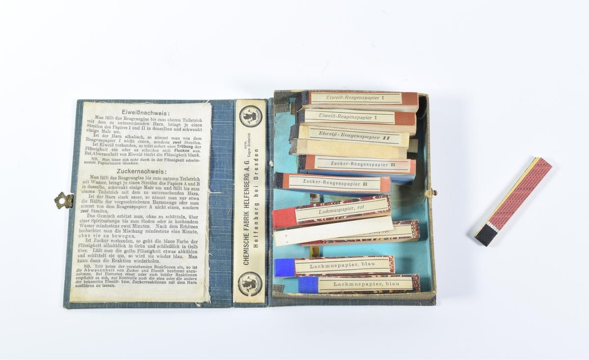 a: En liten blå boks formet som en bok. På forsiden av boksen er det avbildet et reagensrør og en small, buktende papirstripe (lakmuspapir). Boksen inneholder ti blokker med lakmuspapir. Blokkene henger på en tynn stripe metall som er festet til innsiden av boksen. På innsiden av lokket er det limt fast tre stoffark med tekst på tysk.  b: En smal blokk med lakmuspapir som ikke hører til de i boksen.