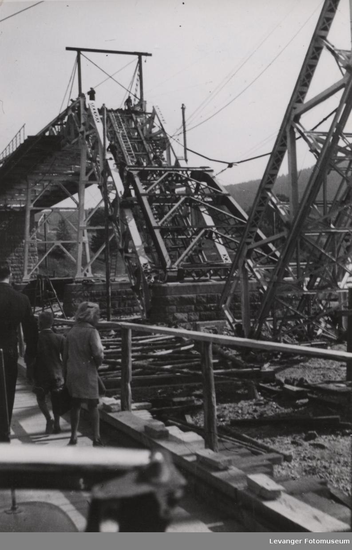 Famile går på den provisoriske broa og ser på den ødelagte Minnesundbroa.