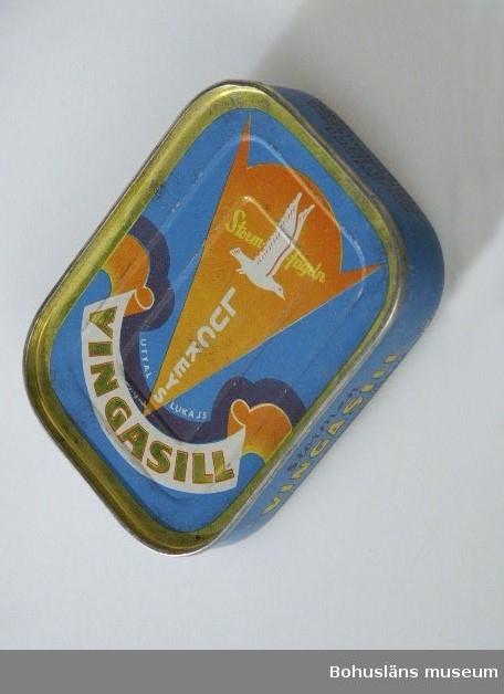 """Rektangulär burk med dekor tryckt direkt på plåten i blått, orange och guldfärg.  Text: """"Luckeys Vingasill Stormfågeln"""". Samma bild och text på båda sidor.  Om givaren se UM026667"""