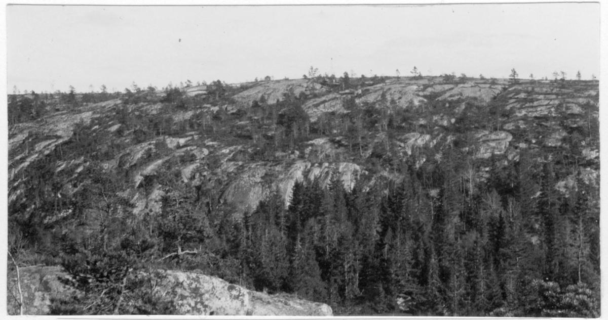 'Bildtext: ''Berget Amundshatt i gränsen mellan Lurs socken (till vänster) och Tanums socken (till höger).'' Vy över delvis trädbevuxet berg, granar. ::  :: Fotonr. 7046:1-84 indelade som ''Landskapsbilder från Göteborgs- och Bohus län.'' Ingår i serie med fotonr. 7046:1-383, 7047:1-33 och 7048:1-67 med bilder från  Länsjägmästare John Lindners bildarkiv.'