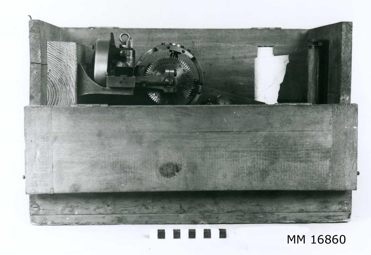 """Gyroskop förvarat i gråmålad trälåda med lock samt ena långsidan öppningsbar med gångjärn och hakar. Till gyroskopet hör en skrivare som går att reglera med spak från lådans utsida. Vev med trähandtag tillkommer samt kopparrör med nippel (för att ge gyroskopet luft). Pappersetiketter på lådans utsida= """"Fr Stockholms Centr 977"""" samt """"Karlskrona""""."""