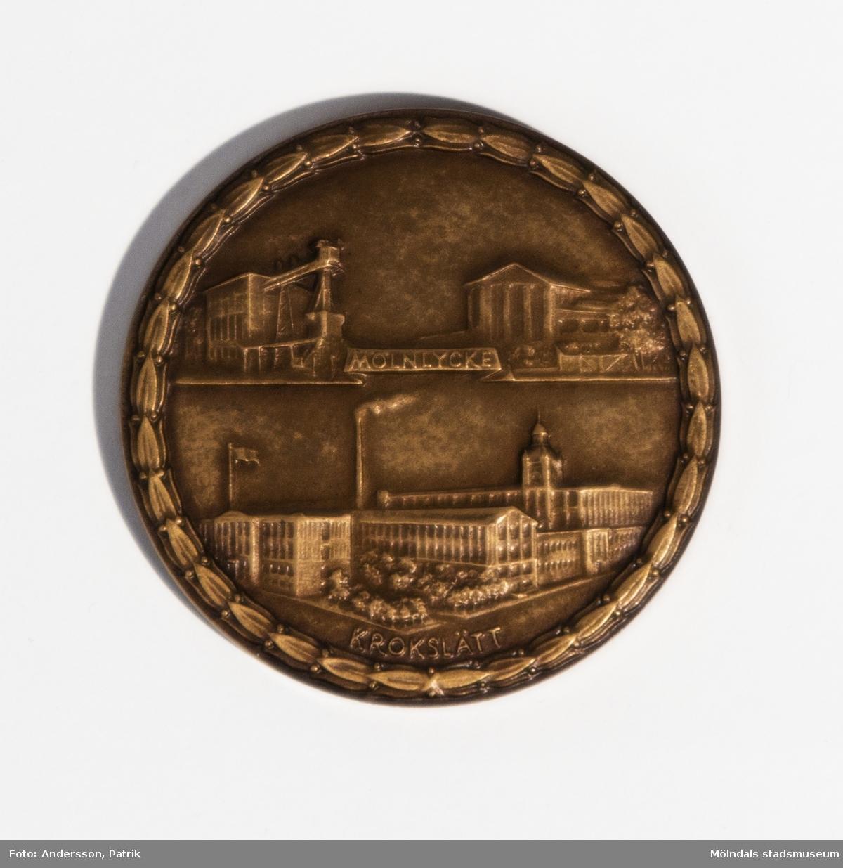 """Minnesmynt i brons från Mölnlycke väfveri AB, utgivet 1849-1949.  Minnesmyntet ligger i en grön orginalförpackning. Förpackningen är av papp. På undersidan finns texten: """"C.C. SPORRONG & CO. KUNGSGATAN 17. STOCKHOLM"""".  På myntets ena sida finns en örn med texten """"1849-1949 MÖLNLYCKE VÄFVERI AKTIEBOLAG"""" gjutet i myntet.  På andra sidan finns Mölnlycke väfveri och Krokslätts fabriker gjutna."""