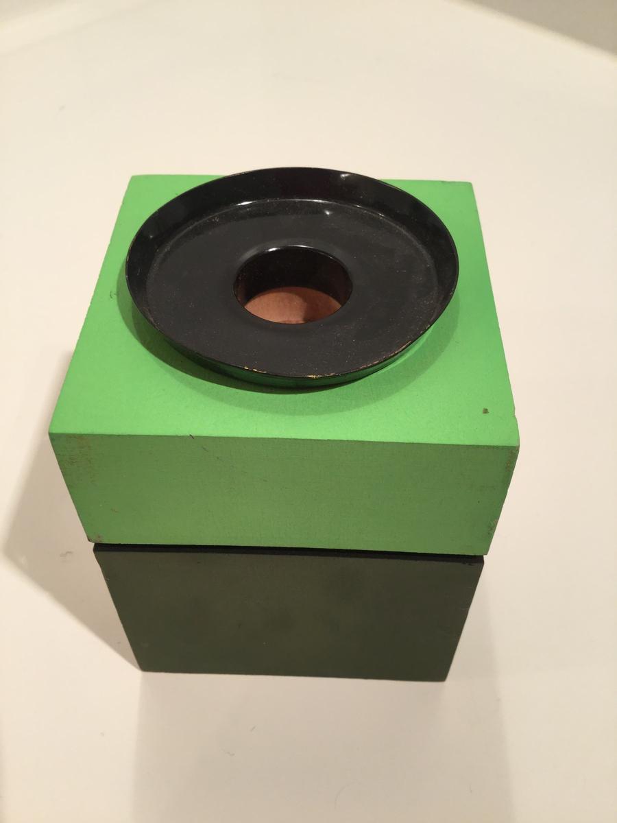 Ljusstake i målat trä (två gröna nyanser) med ljushållare i svart metall.