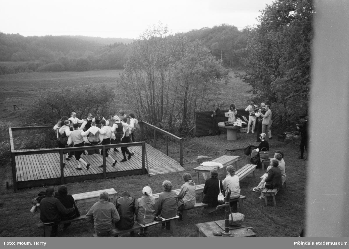"""Gammeldans i Långåker, Kållered, år 1983. """"Kvarnby folkdanslag och Kållereds Spelmanslag värmer upp publiken en kall sommarkväll på Långåker.""""  För mer information om bilden se under tilläggsinformation."""
