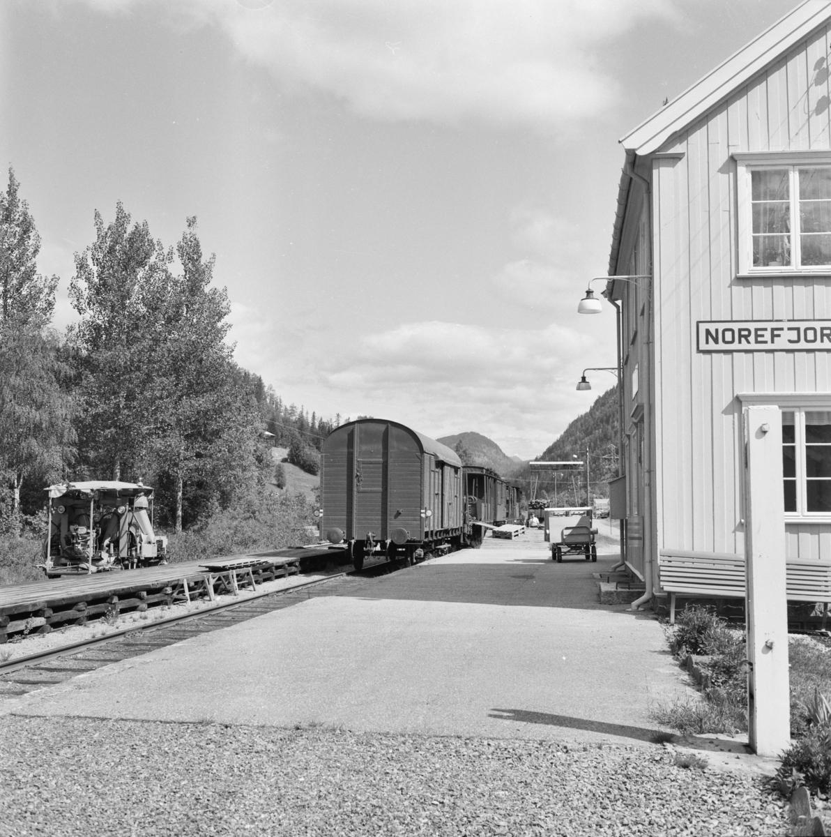 Godstog 5397 har stoppet på Norefjord stasjon for av- og pålessing av stykkgods. Til venstre en motorisert arbeidstralle for baneavdelingen.