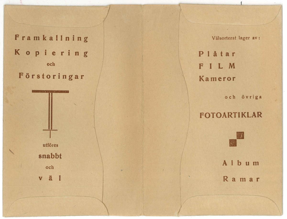 Kuvert för kort och negativ. Från företaget Fotomagasinet Rapid som låg på Sundsgatan 12 i Vänersborg. Motivet på kuvertet är en kvinna stående hållandes en kamera och en avtryckare som är fäst med sladd till kameran. Hon är klädd i en basker och en flygande halsduk. Mode runt 1920-talet.  Kuvertet är riktad till Lindgren. Endast framkallning var beställd.  Inuti finns reklam för olika produkter som man kan beställa.