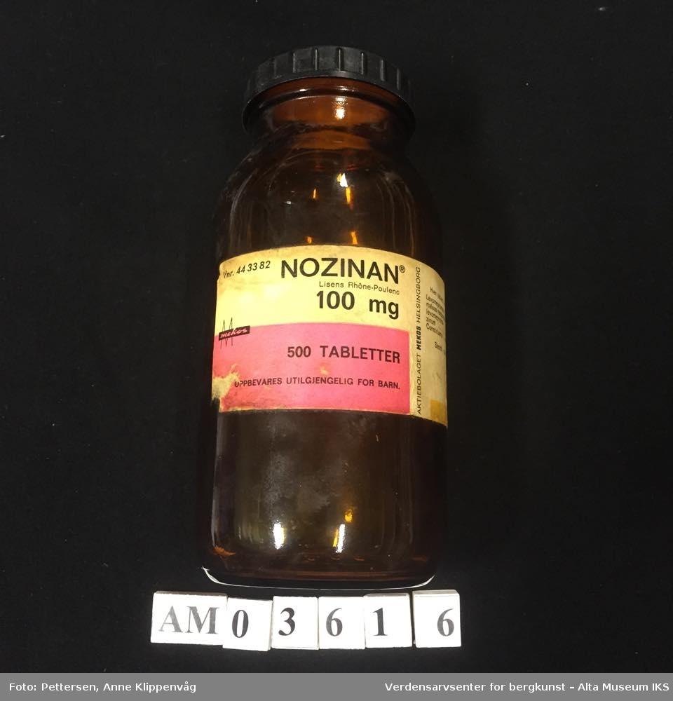 Sylinderformet medisinflaske i brunt glass. Sort plastlokk med riller. Pålimt papiretikett.