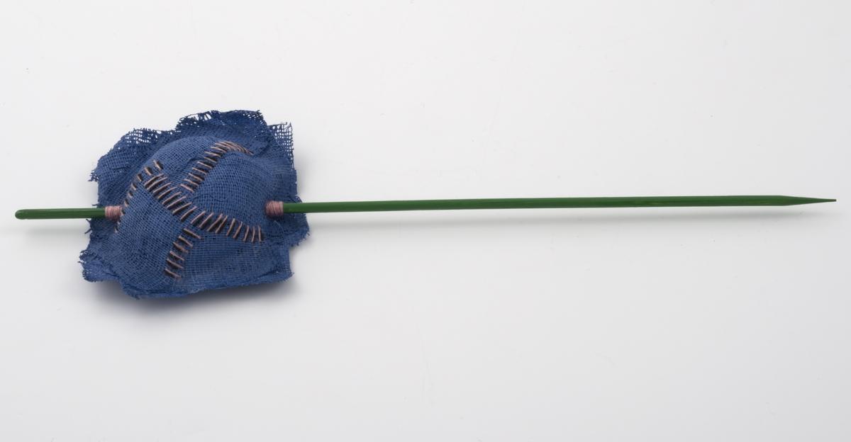 En rektangulær og malt pute av gas med broderte sting er tredd på en malt trepinne. Trepinnene er av typen spidd. Gasputen er festet med trå ved spiddets inngang og utgang. Flat bakside. Trepinnen er grønn mens puten er blå med rosa og svarte sting.