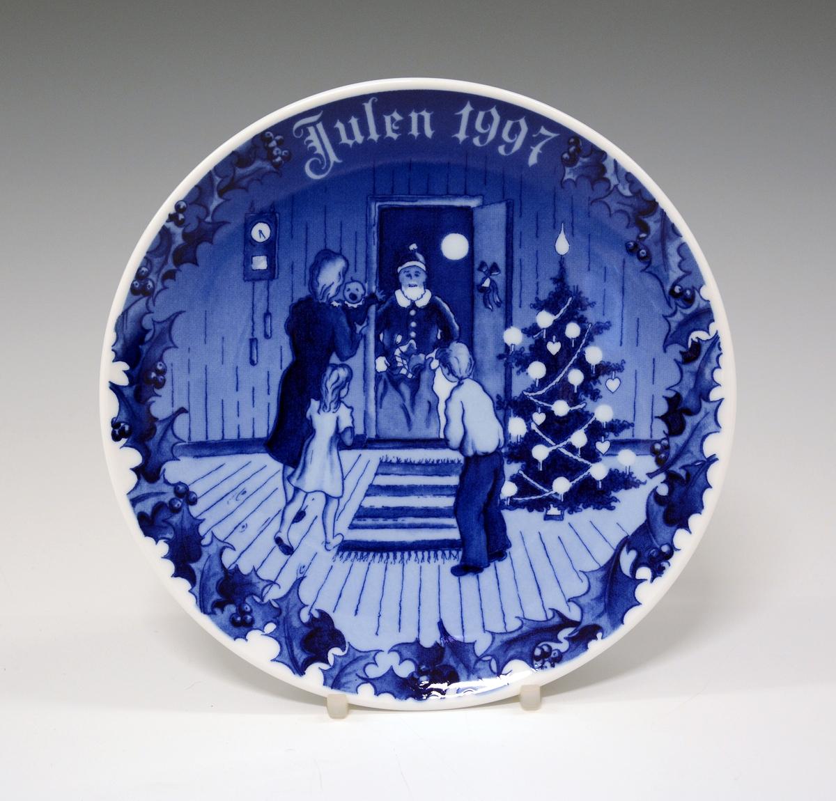 Juleplatte av porselen. Glatt modell. Hvit glasur. Dekorert med stueinteriør, mennesker og tekst Julen 1995 i ulike blåfarger. Dekor av Thor Henning Kristiansen.
