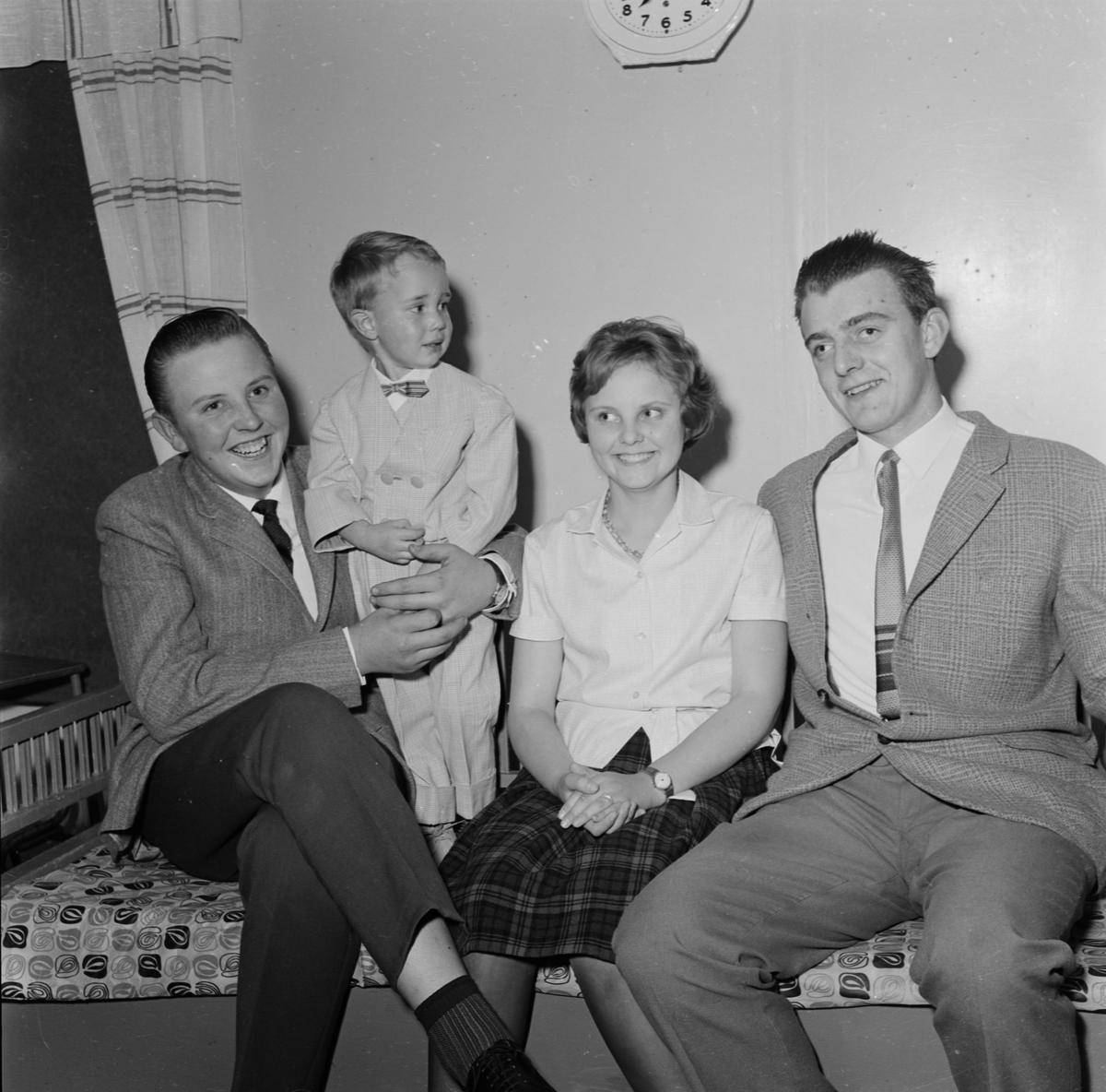 Kvinna, man och barn sitter i soffa, Uppland