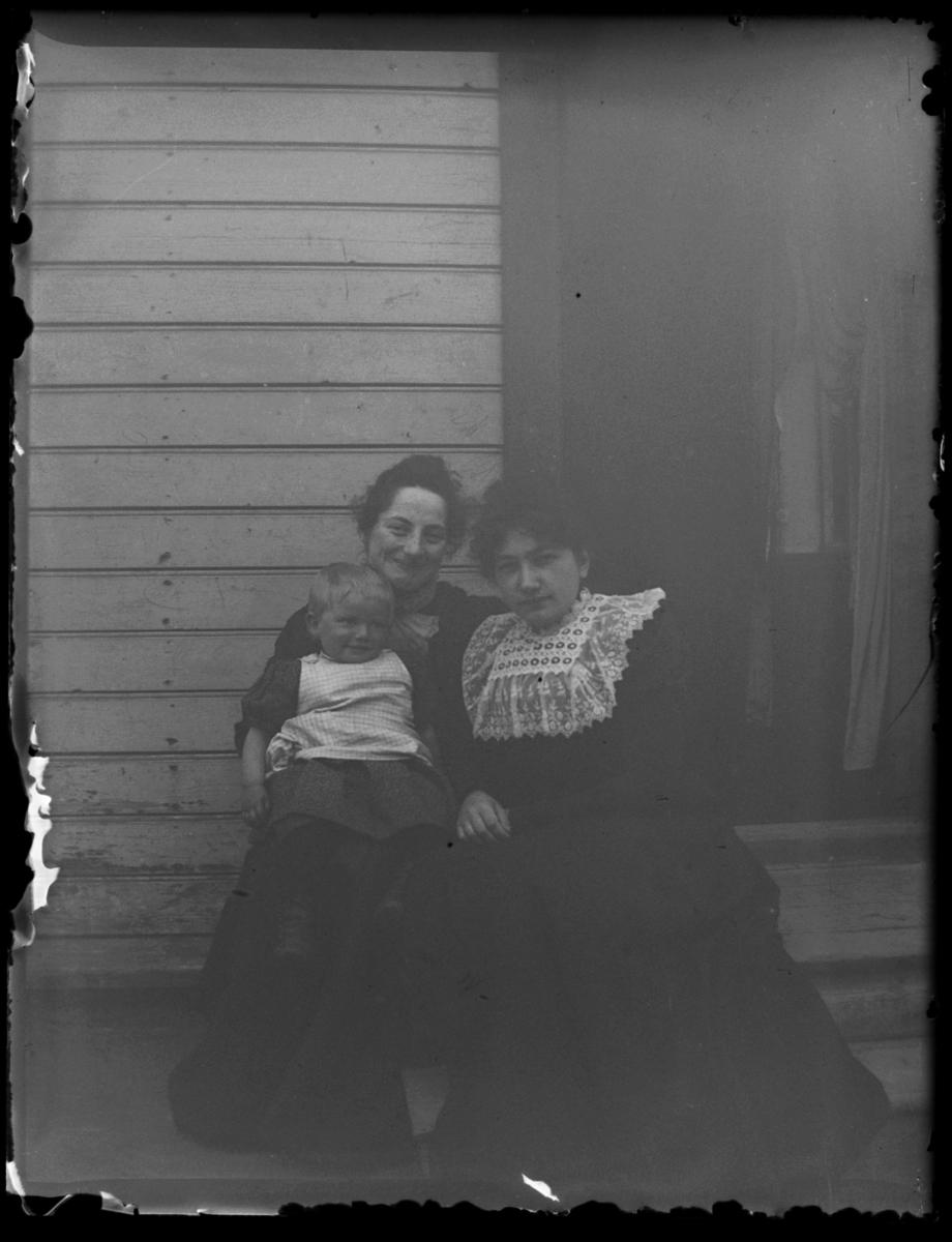 To kvinner sittende på en trapp ute med et barn på fanget