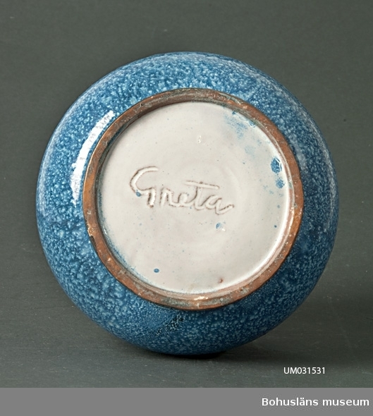 Klotrund vas med dekor av pålagd bladsinga i relief. Vit engobe med blå glasyr. I botten handskriven signatur: Greta